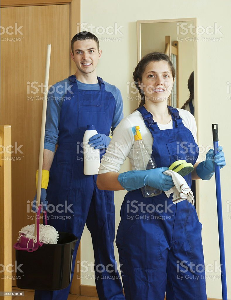 Handsome cleaners cleaning room stock photo