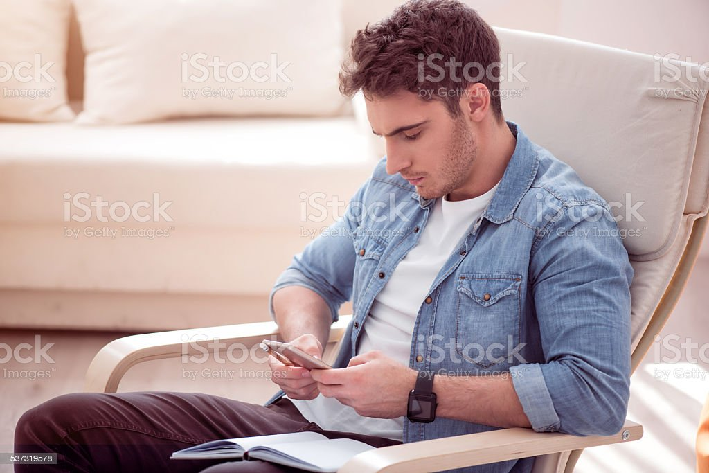 Handsome concentrated man  sitting in the armchair stock photo