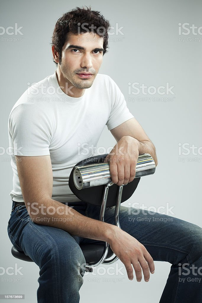 Handsome, confidant man casually sitting on chair holding rolled-up magazine stock photo