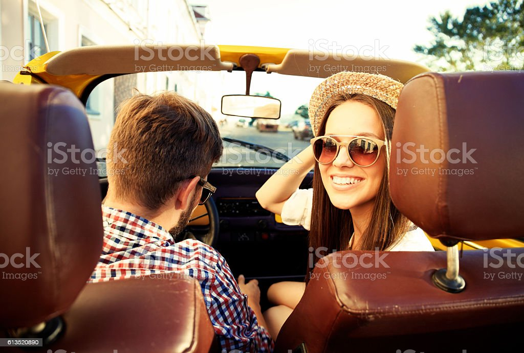 handsome couple looking at camera sitting in car stock photo