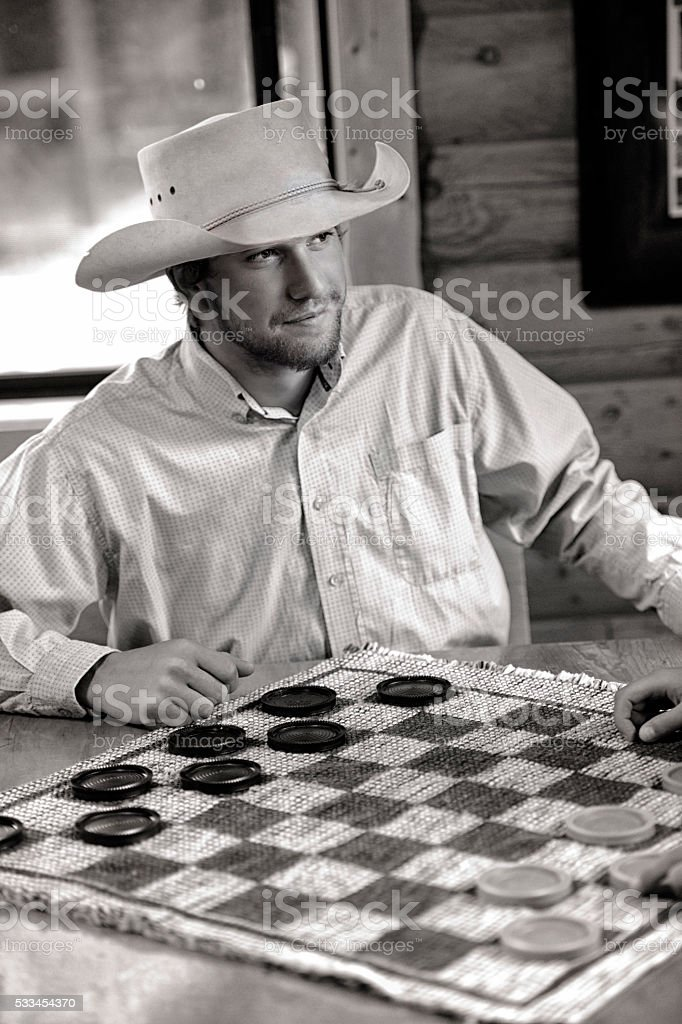 Handsome Cowboy Playing Checkers stock photo