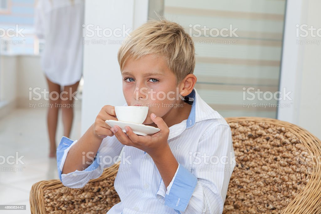 Handsome cute blond boy drinking coffee, woman on background stock photo