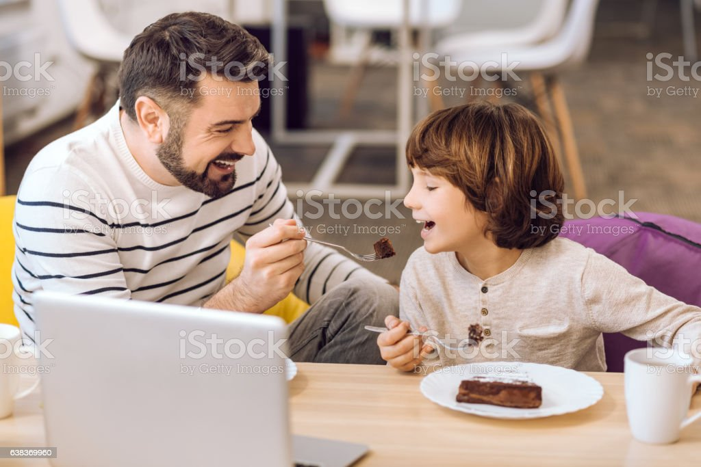 Handsome daddy feeding his son stock photo