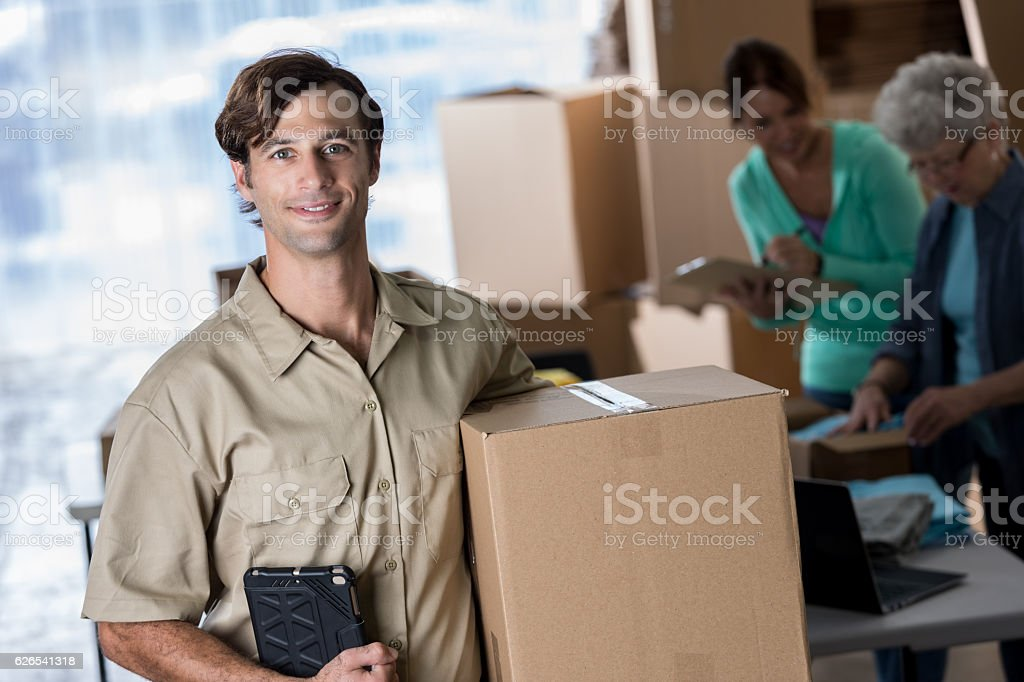 Handsome deliveryman with package in distribution warehouse stock photo