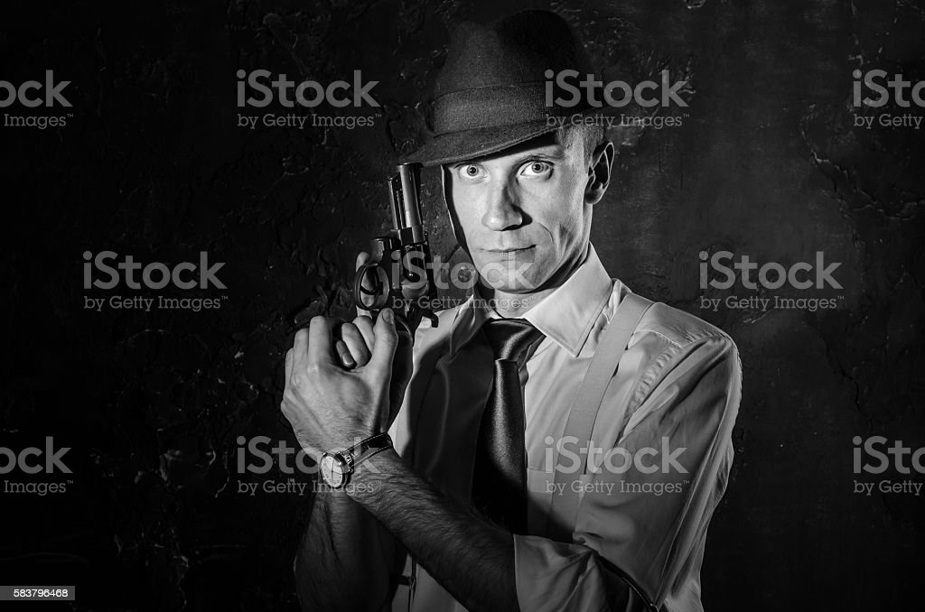 Handsome detective in hat holding a gun in the dark stock photo