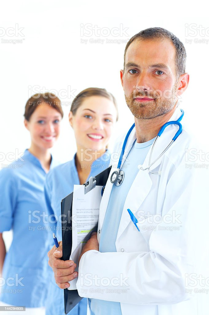 Handsome doctor with two nurses in the background royalty-free stock photo