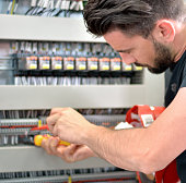 Handsome Electrician Working With Work Tool in Electrical Room