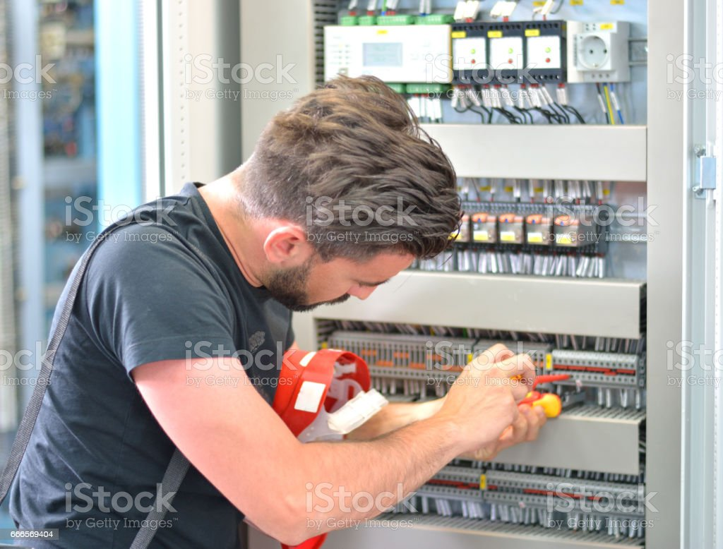 Handsome electrician working with work tool in electrical room stock photo