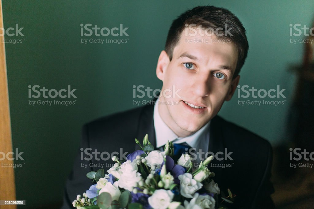 Handsome elegant groom in black suit with a wedding bouquet stock photo