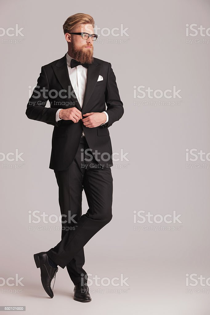handsome elegant man closing his jacket. stock photo