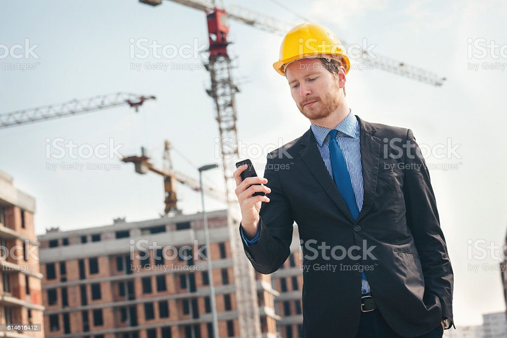 Handsome engineer at construction site using smart phone stock photo
