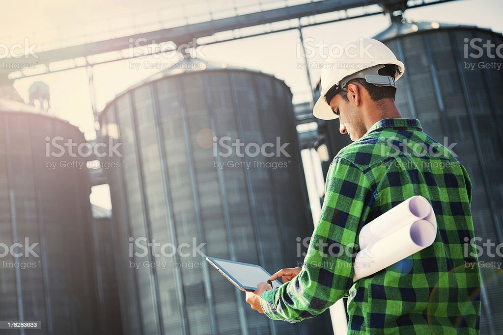 Handsome engineer taking notes on a digital tablet royalty-free stock photo