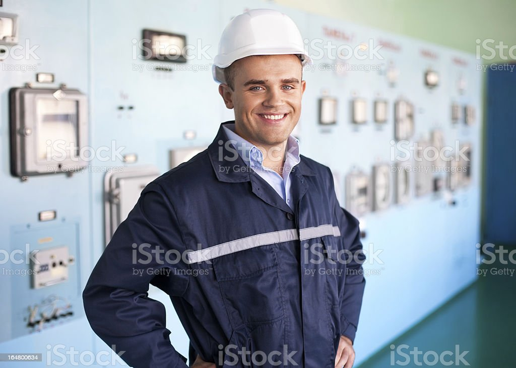 A handsome engineer wearing a hard hat in the control room stock photo