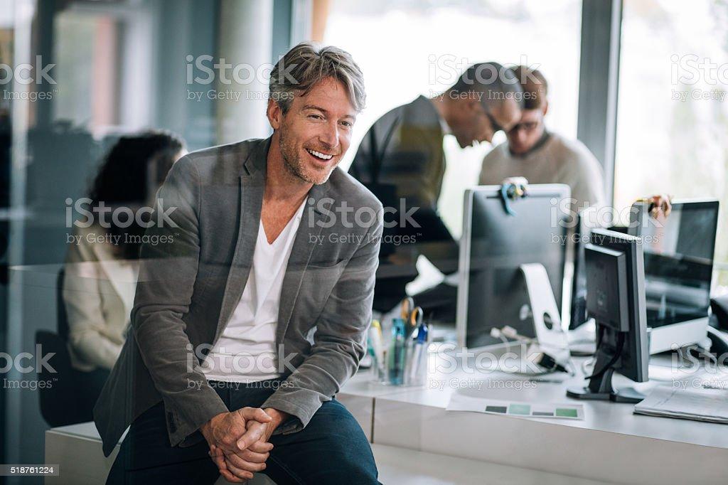Handsome executive sitting smilling through window stock photo