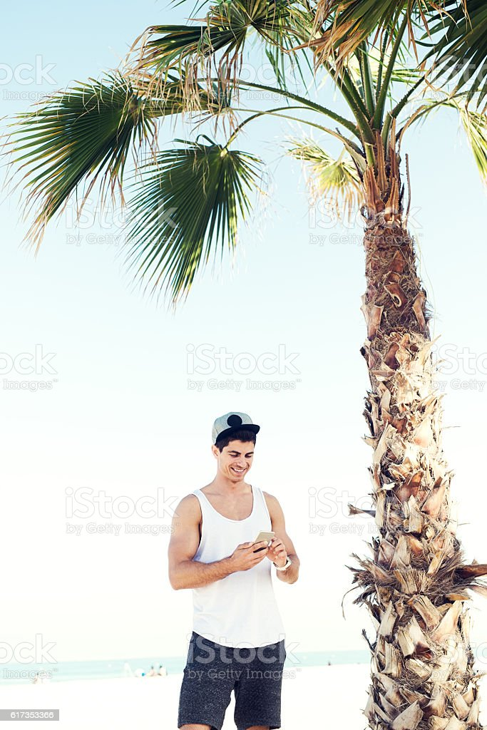 Handsome fashion model looking at smart phone at beach. stock photo