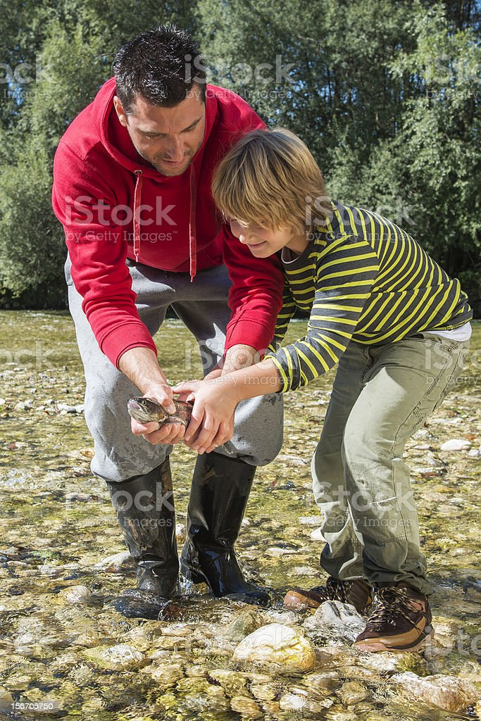 Handsome father and his boy carefully hold caught fish royalty-free stock photo