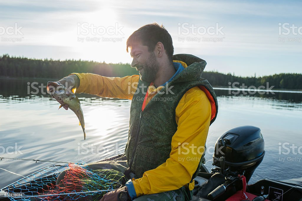 Handsome fisherman catched a haddock in the sea stock photo