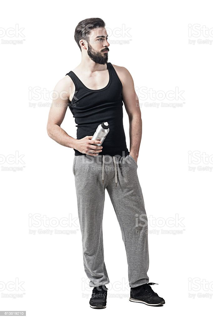Handsome fit young man holding water bottle container looking away stock photo