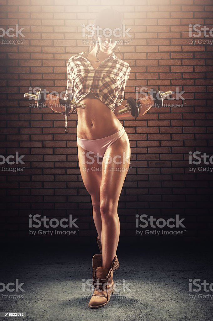 Handsome fitness model working out with dumbbells stock photo