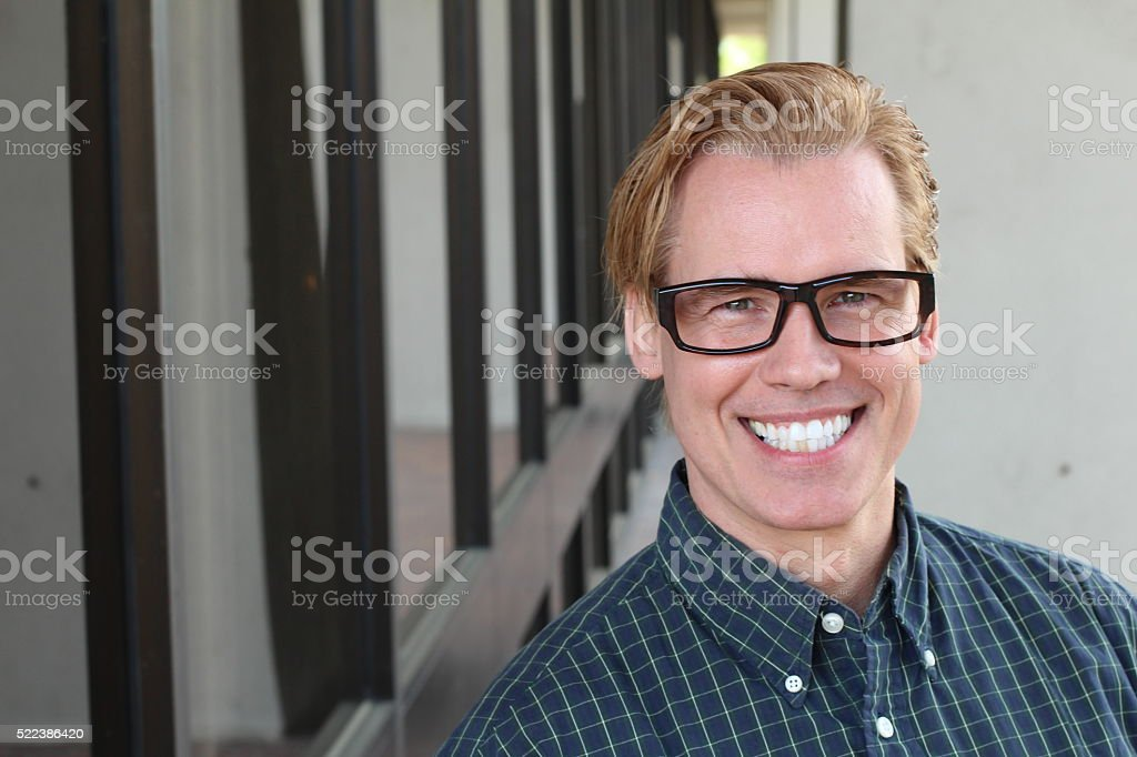 Handsome gay blonde man wearing intellectual glasses stock photo