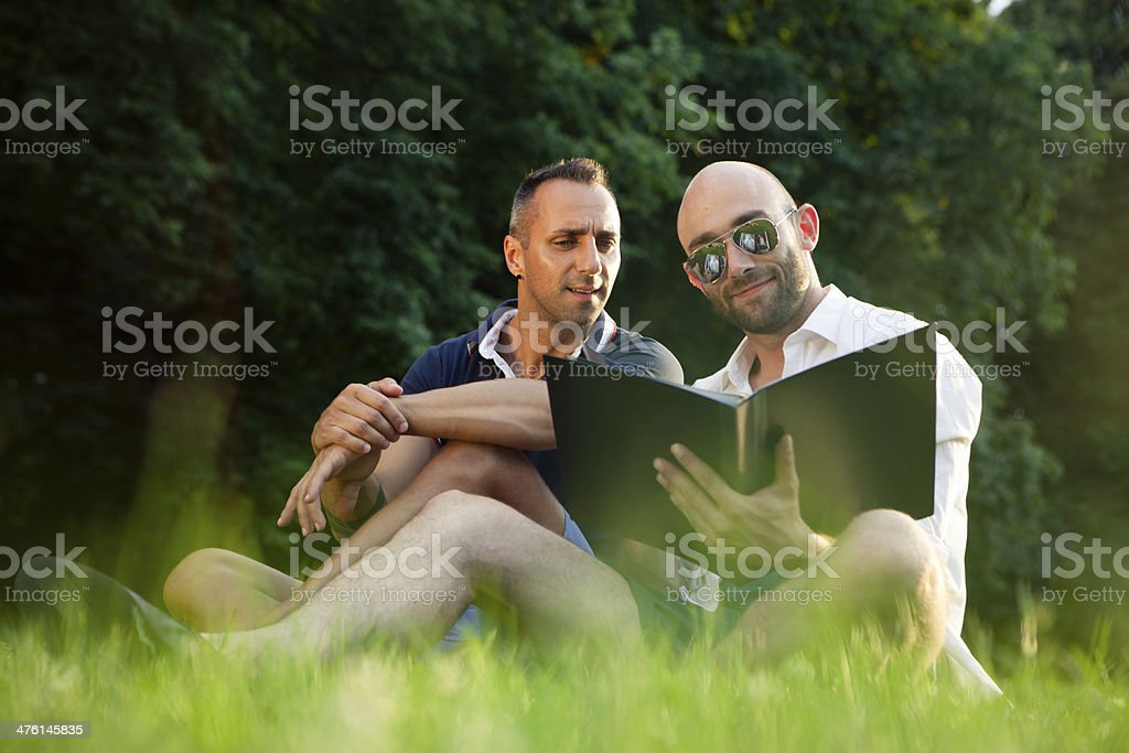 handsome gay couple relax together in the park royalty-free stock photo