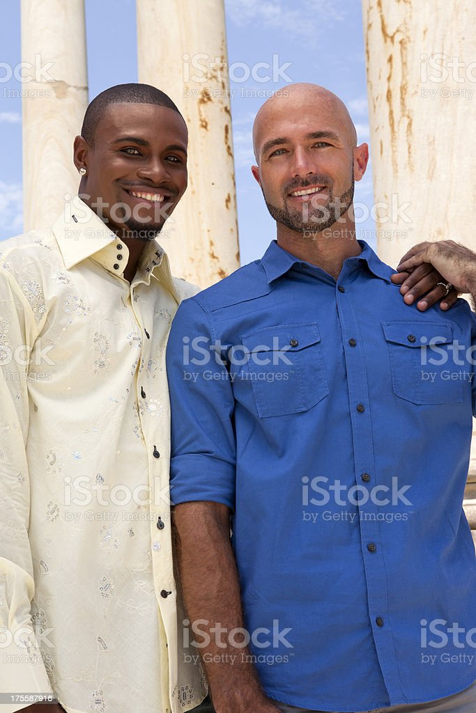 A handsome gay couple smiling while holding hands stock photo