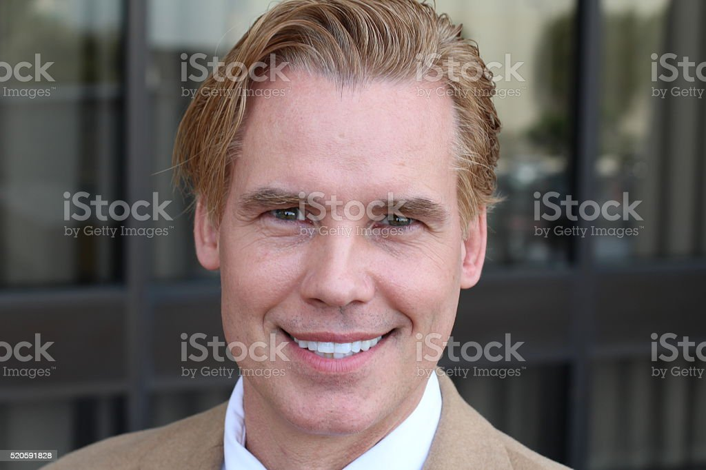 Handsome gay middle-aged blonde man stock photo
