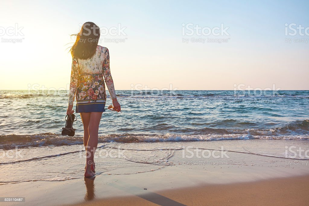 handsome girl lookingl far away at the sunset near ocean stock photo