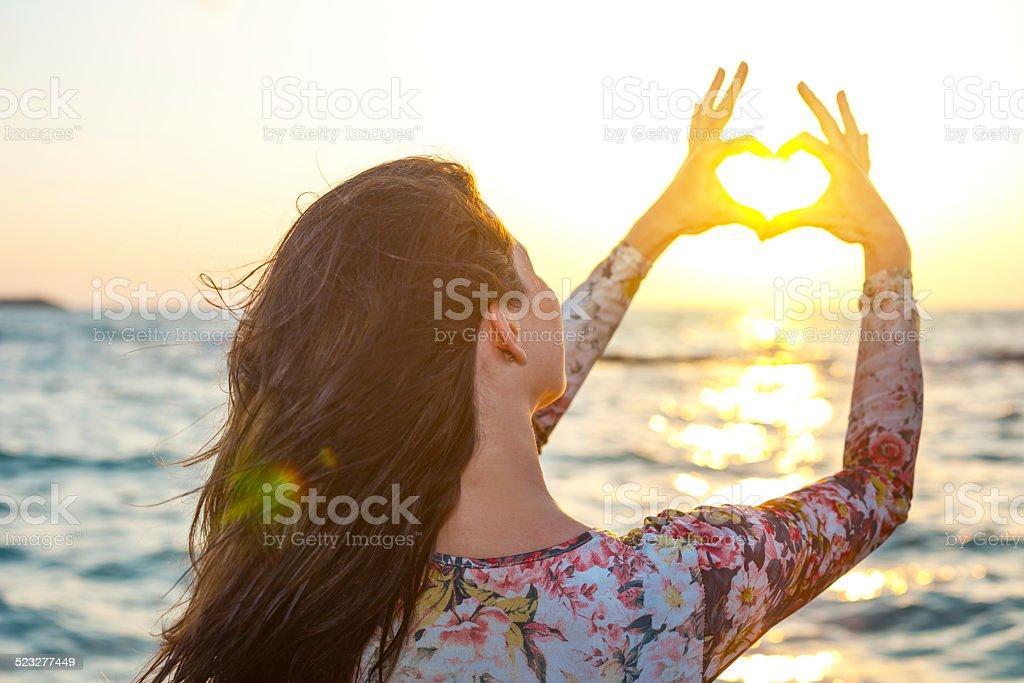 handsome girl making heart round the sun stock photo