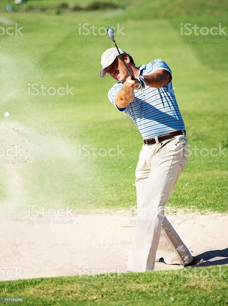 Handsome golfer chipping from a sand pit stock photo