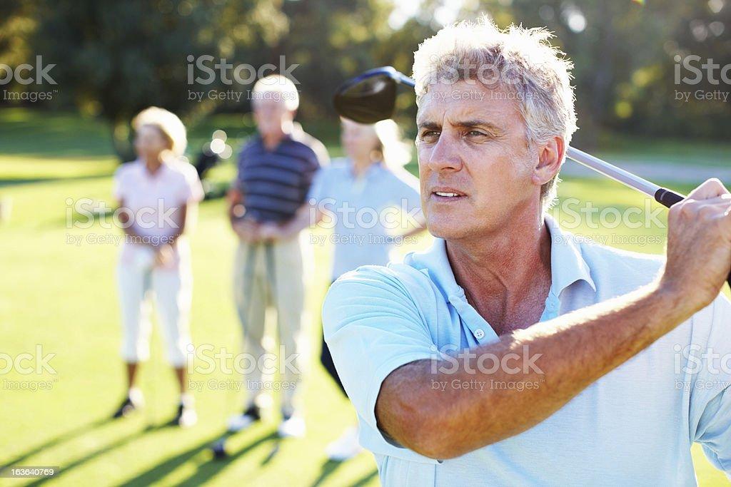 Handsome golfer swinging stock photo