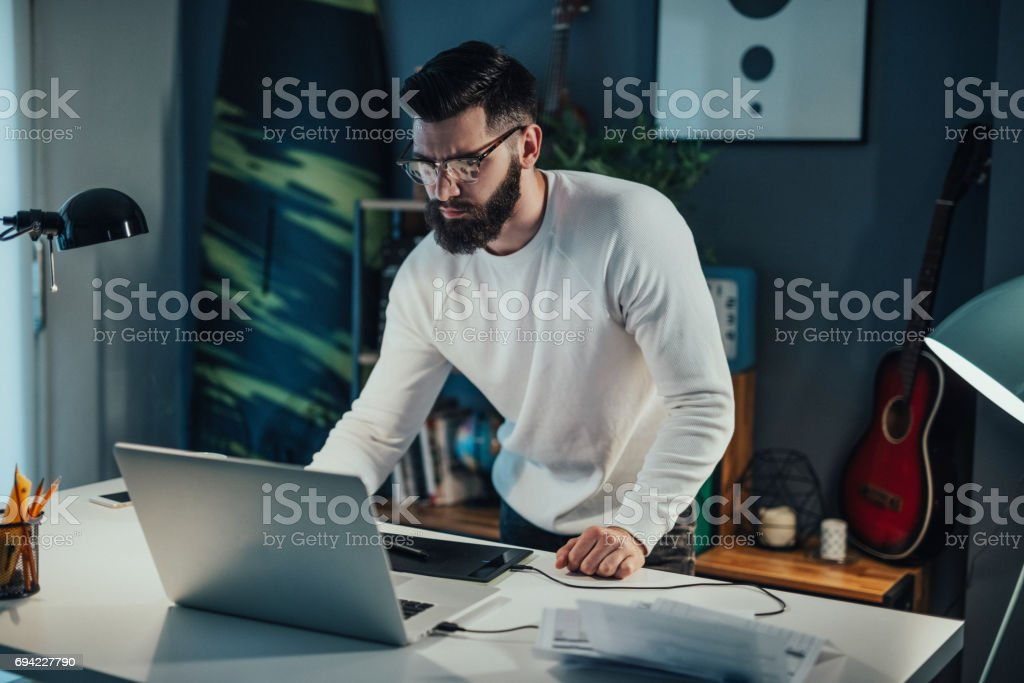 Handsome graphic designer working from home office stock photo