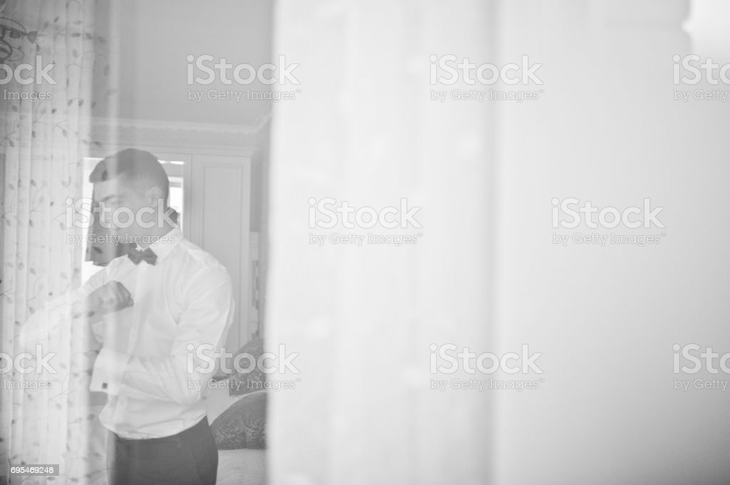 Handsome groom dressing up and getting ready for his wedding in the room. stock photo
