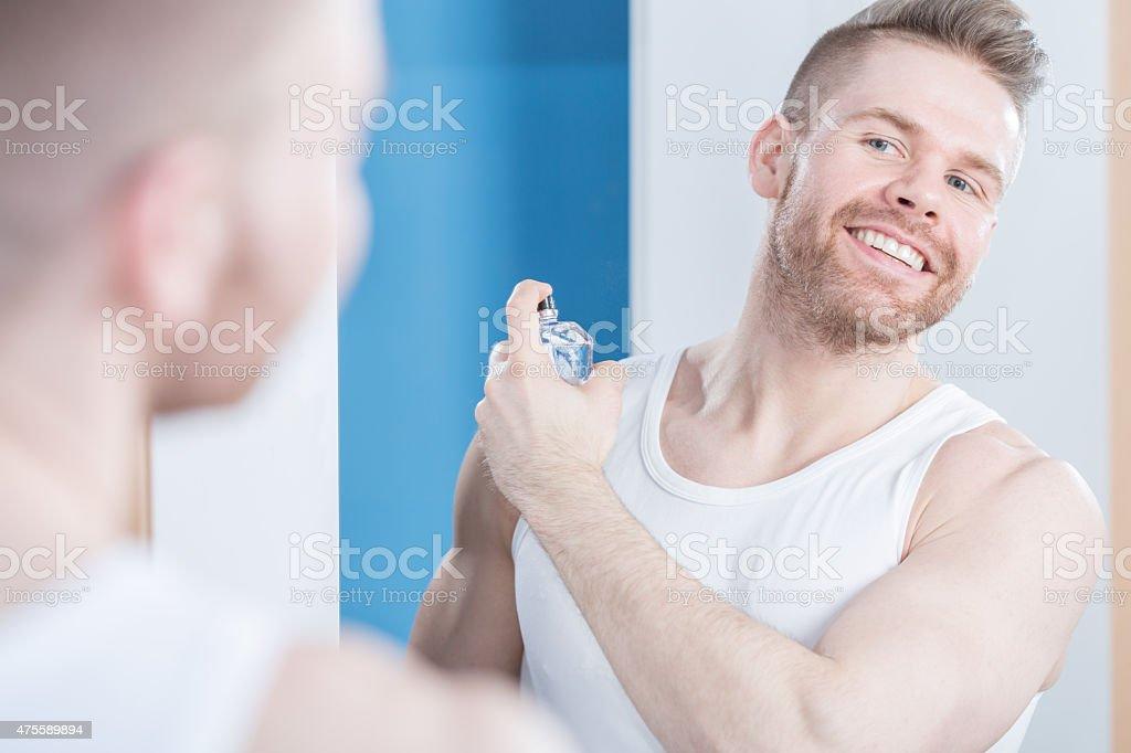 Handsome guy applying perfume stock photo