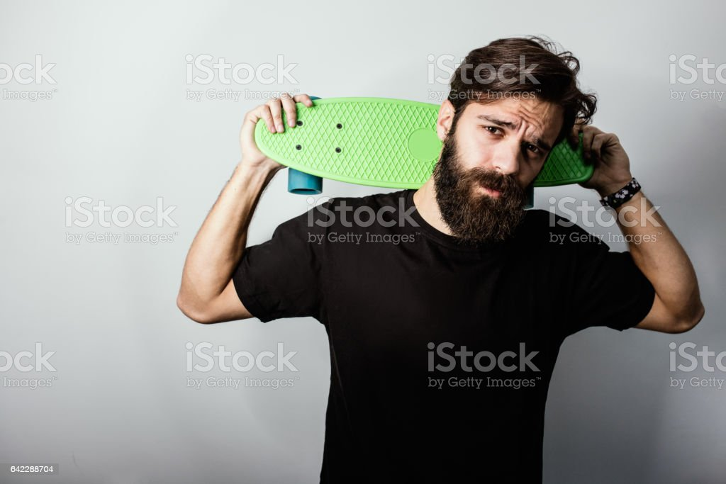 Handsome guy holding penny skateboard on his shoulders stock photo