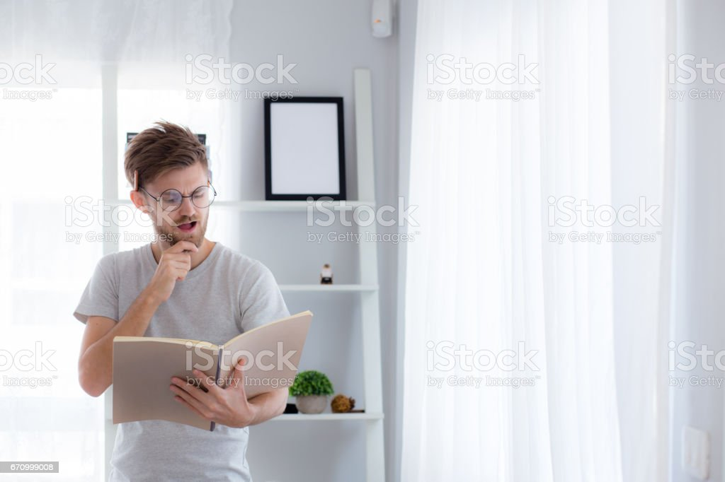 Handsome guy in eyeglasses is reading book preparing exam and thinking with standing at the living room - education concept. stock photo