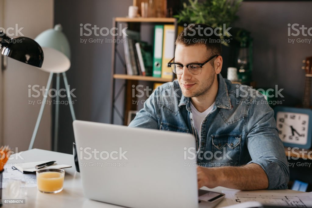 Handsome guy in the living room using a laptop stock photo