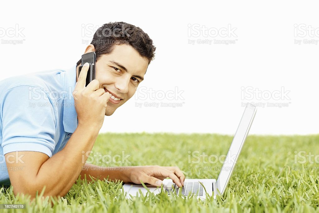 Handsome guy lying on grass using laptop and cellphone royalty-free stock photo