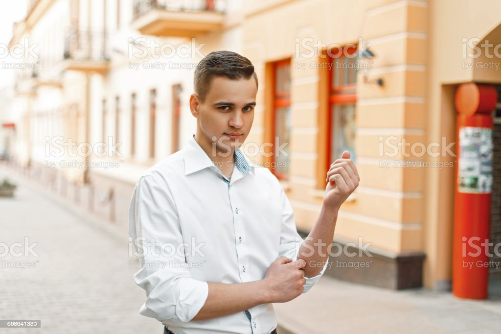 Handsome guy manager in a white shirt in the city stock photo