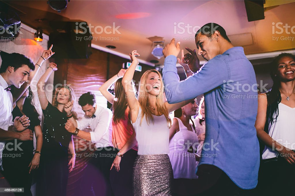 Handsome guy of African descent dancing with girlfriend in club stock photo
