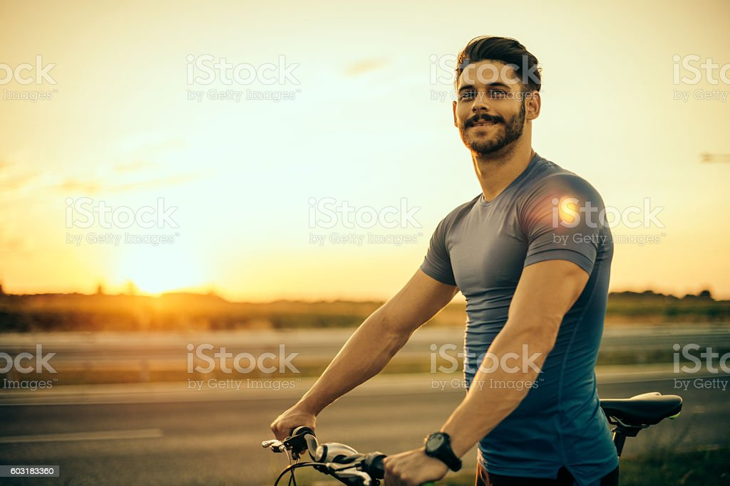 Handsome guy riding mountain bike in sunset stock photo