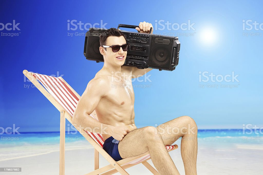 Handsome guy sitting on a chair with boombox royalty-free stock photo