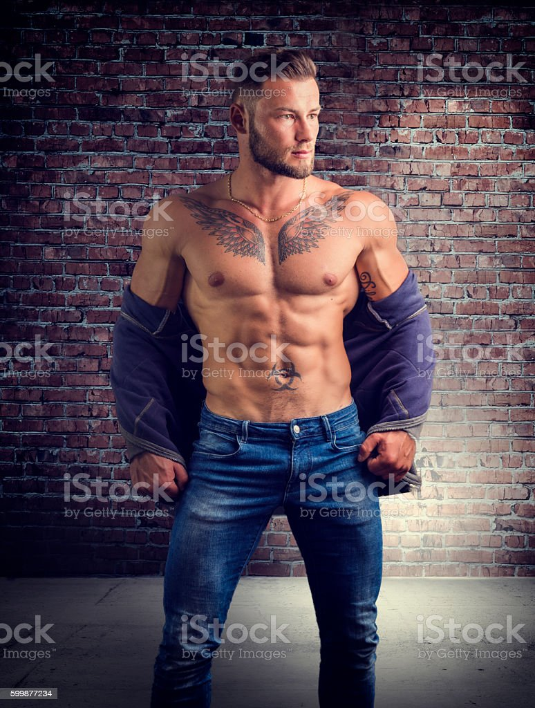 Handsome half-naked muscular man standing stock photo