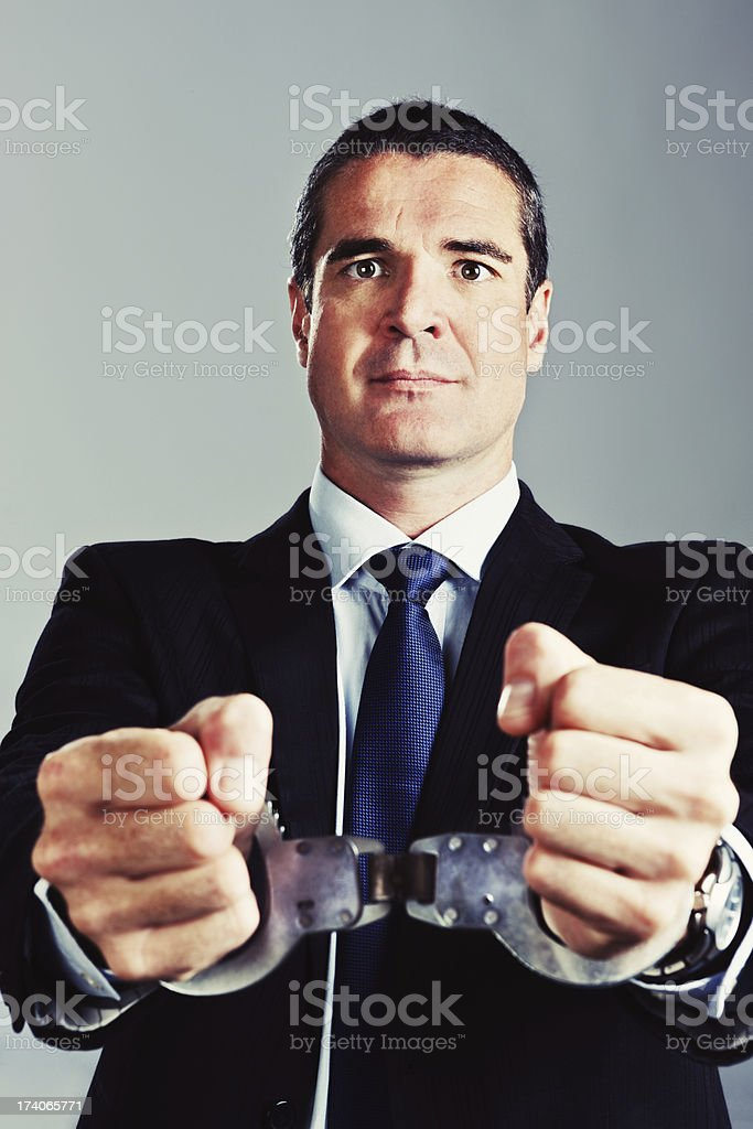 Handsome handcuffed businessman: helpless or white collar criminal royalty-free stock photo