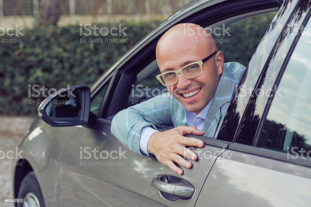 Handsome happy business man male looking back out of window showing his new car stock photo