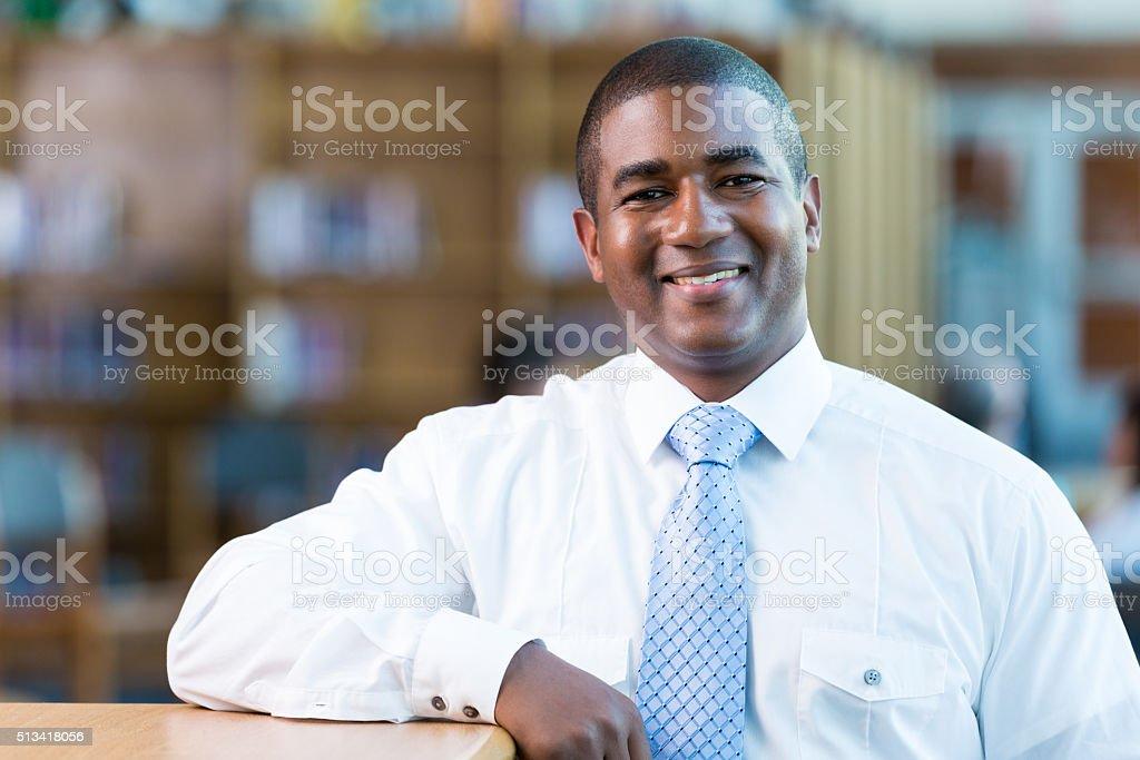 Handsome high school teacher in school library stock photo