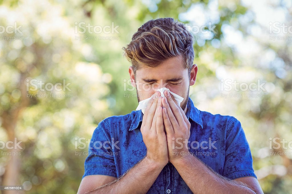 Handsome hipster blowing his nose stock photo