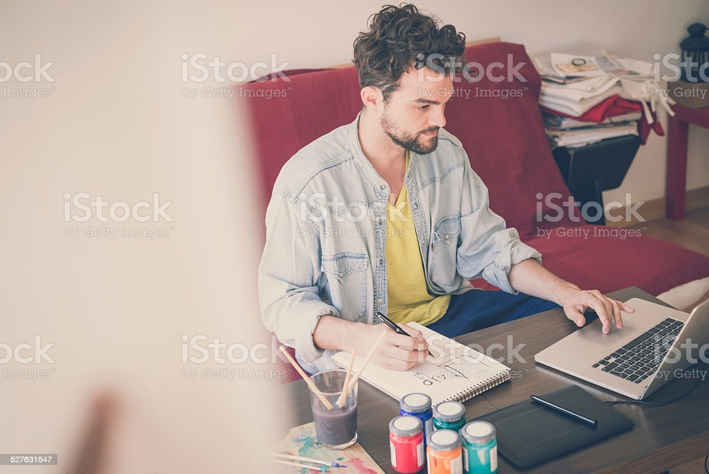 handsome hipster modern man working home using laptop stock photo