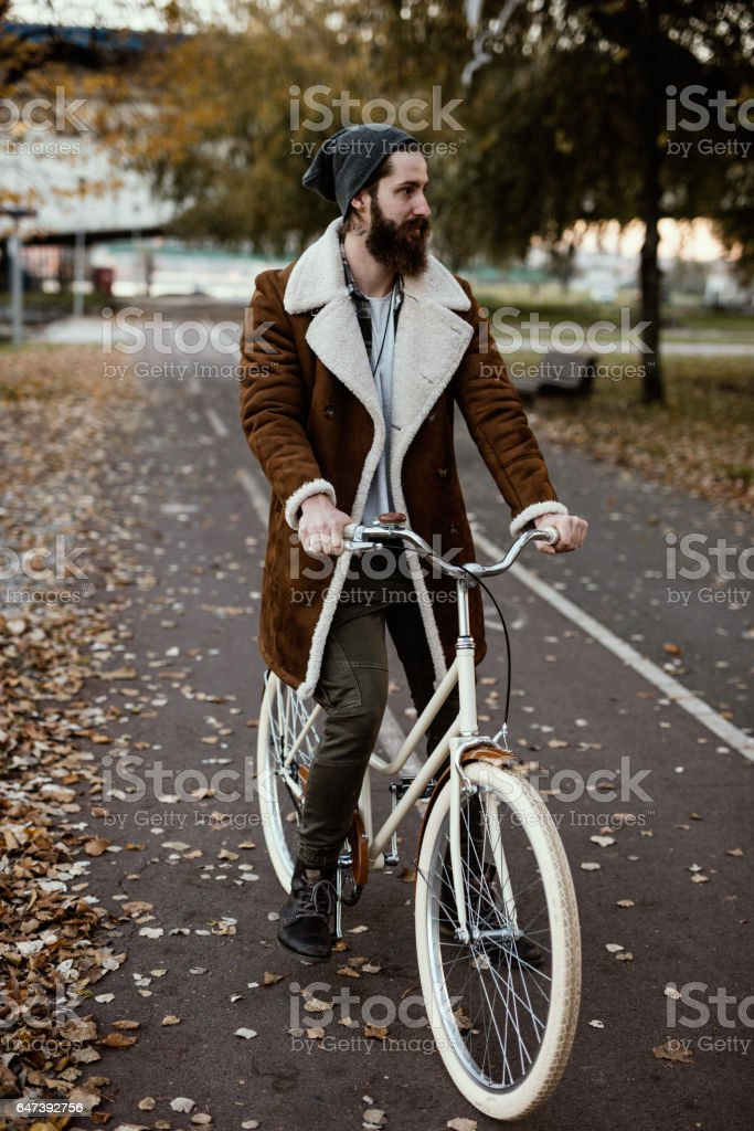 Handsome hipster on a vintage bicycle in the park stock photo