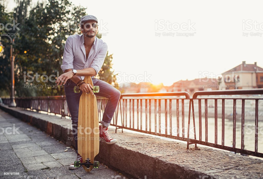 Handsome hipster with longboard stock photo